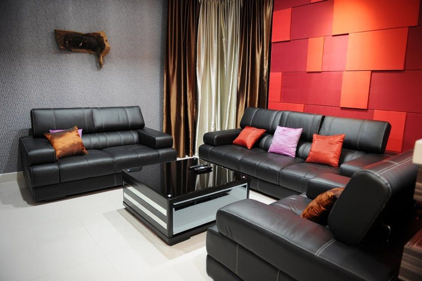 Bright red and orange accent wall in living room with black leather furniture