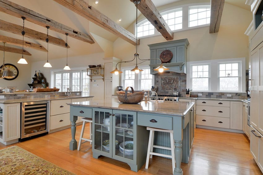Country kitchen with large rustic island, expsoed wood beam ceiling and bright wood floor