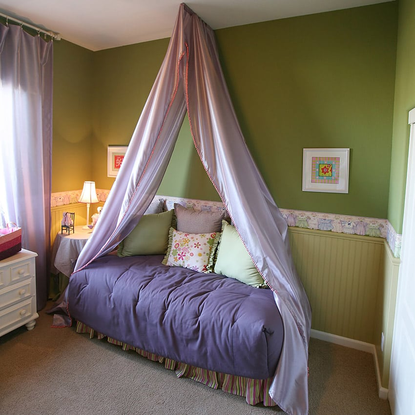 Girls bedroom with purple bed drapery