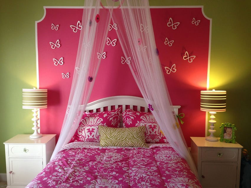 Girls bedroom with-sheer bed curtain and pink accent wall with butterflies