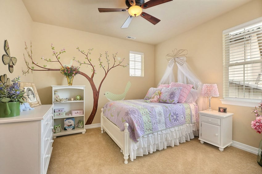 Girls bedroom with wall mural and white furniture