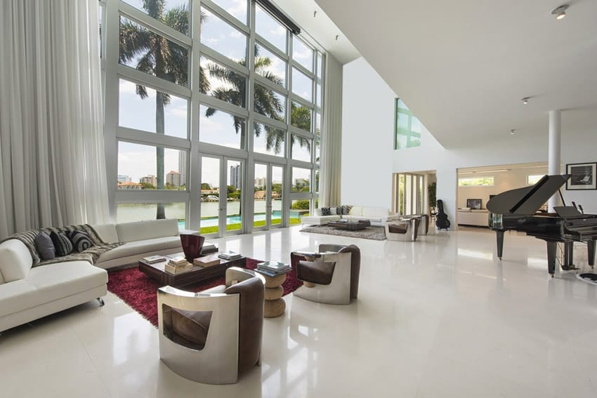 Large modern living room design with high ceilings, water view and grand piano