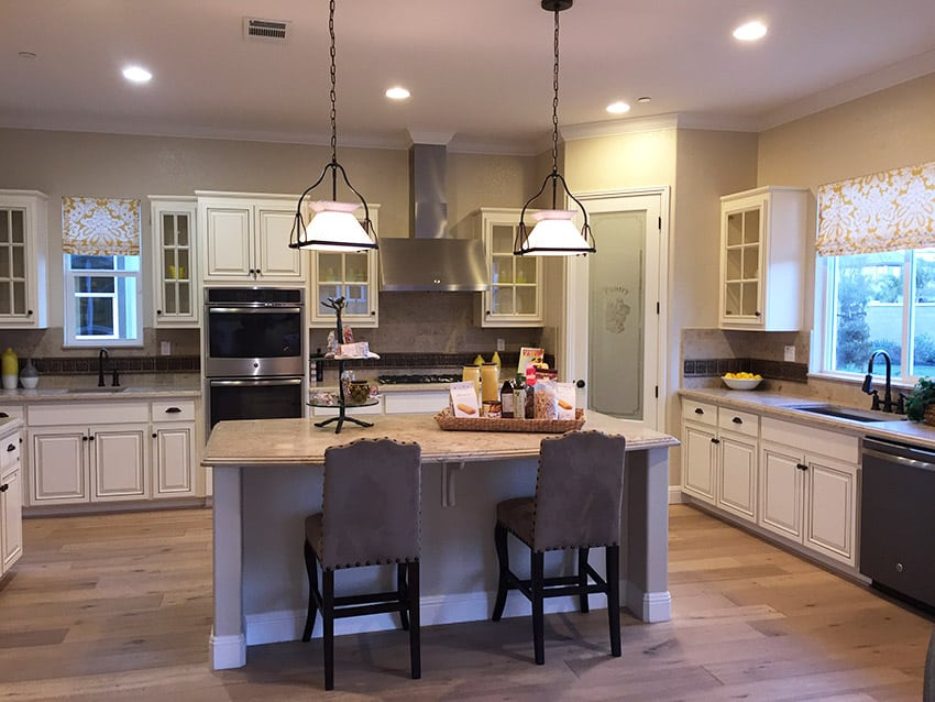 Kitchen in new model home with dining island and white cabinetry