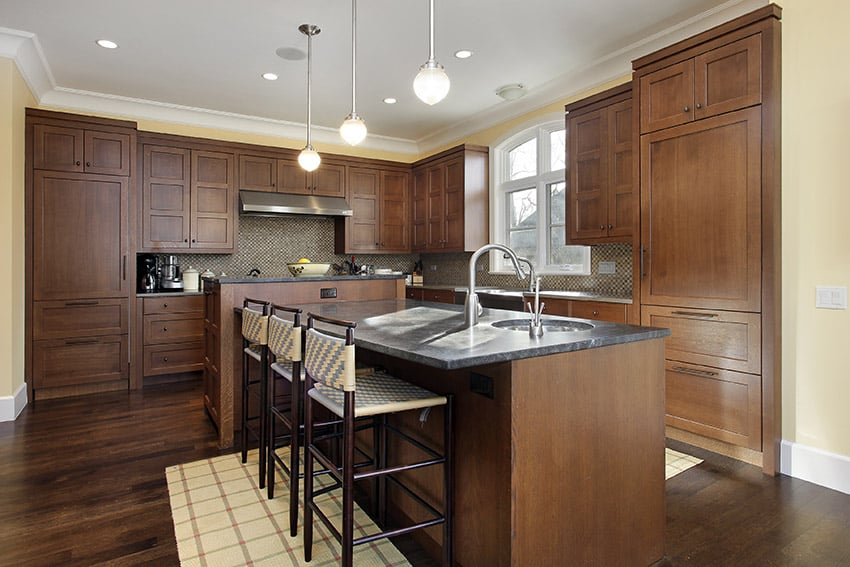 L shape kitchen with island and rich wood cabinetry