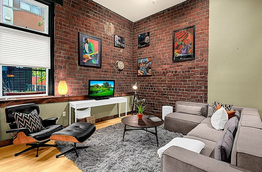 Modern living room with brick wall and light wood flooring