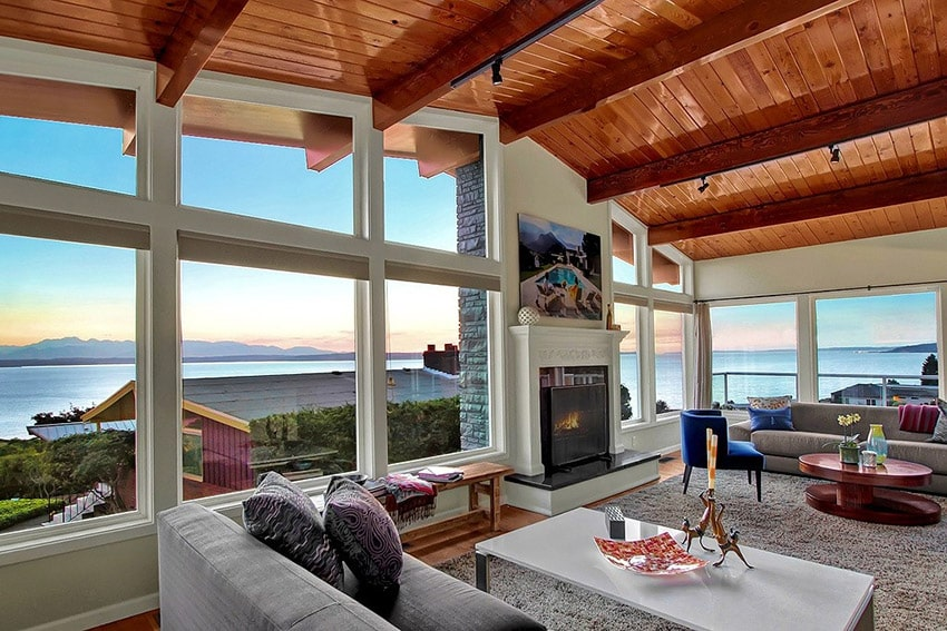 Modern living room with high arched wood ceiling and water views