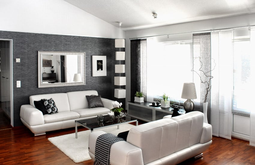 Modern living space with black wallpaper, wood flooring and white couches