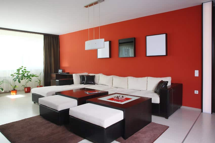 Modern room with red accent wall, black furniture and white cushions