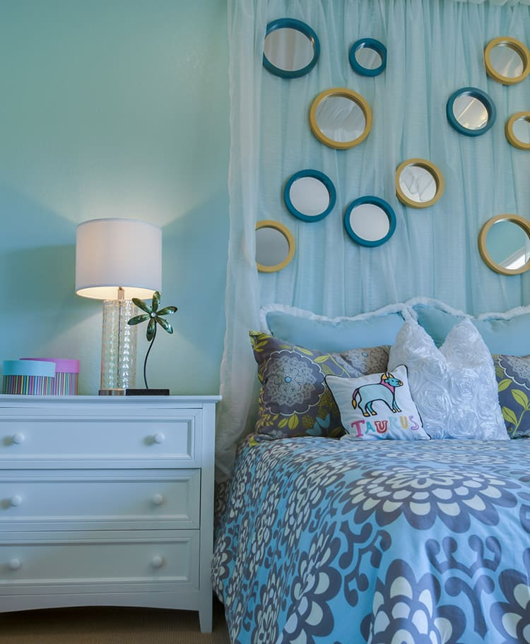 Pretty blue girls bedroom with circular wall mirrors