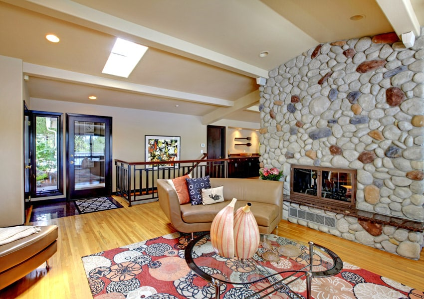 River rock fireplace in modern room with light wood flooring and brown leather furniture