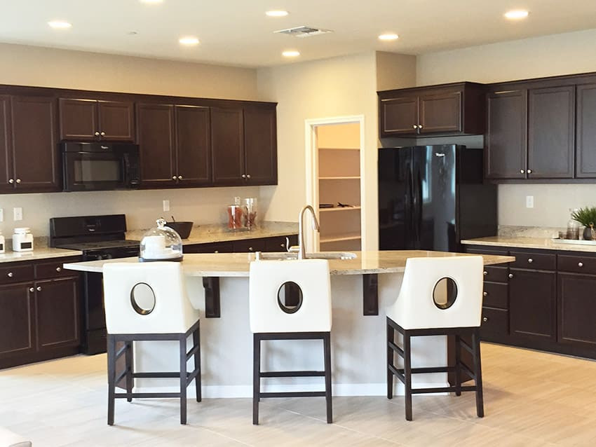 White kitchen island in dark brown cabinet kitchen