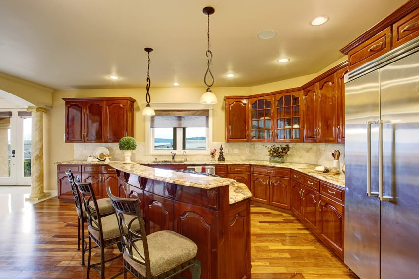 Bright traditional kitchen with polished wood floors and breakfast bar