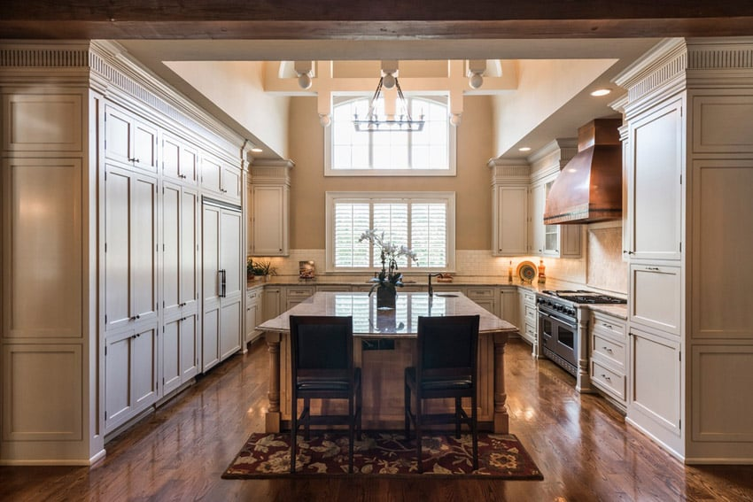 Closed kitchen with high ceilings and calcutta gold granite counters