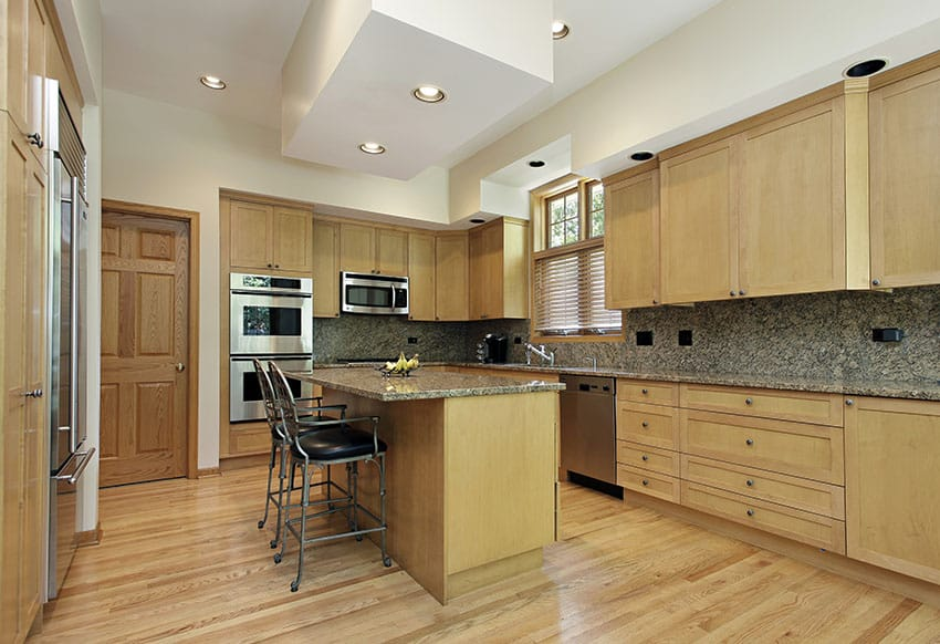 kitchen with island for dining and light maple wood cabinets