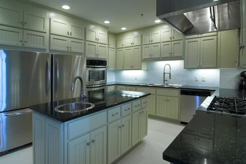 Light yellow kitchen with black countertops