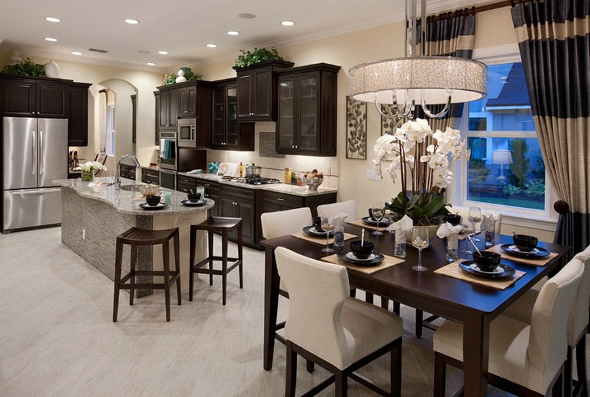Transitional style kitchen design with dark cabinetry dining area