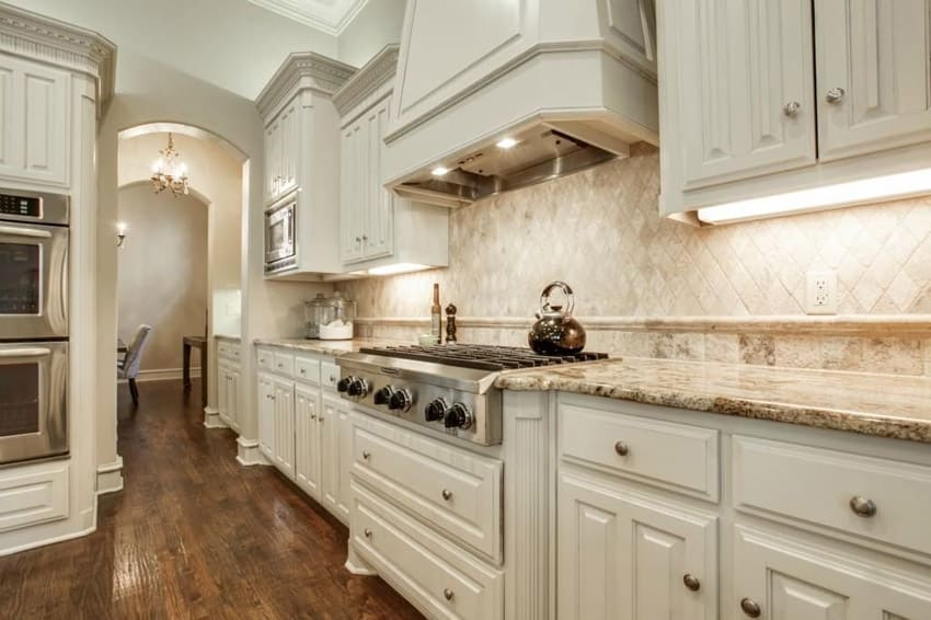 White kitchen with barricato granite counters decorative oven hood