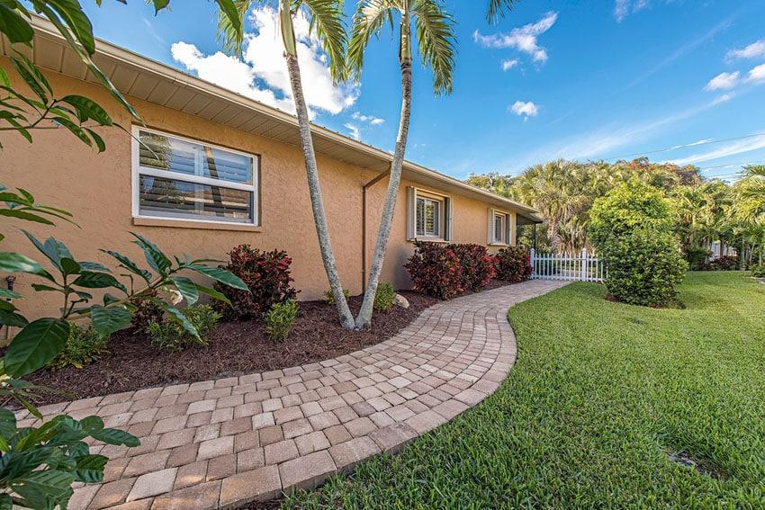 Brick paver walkway past grass and around home