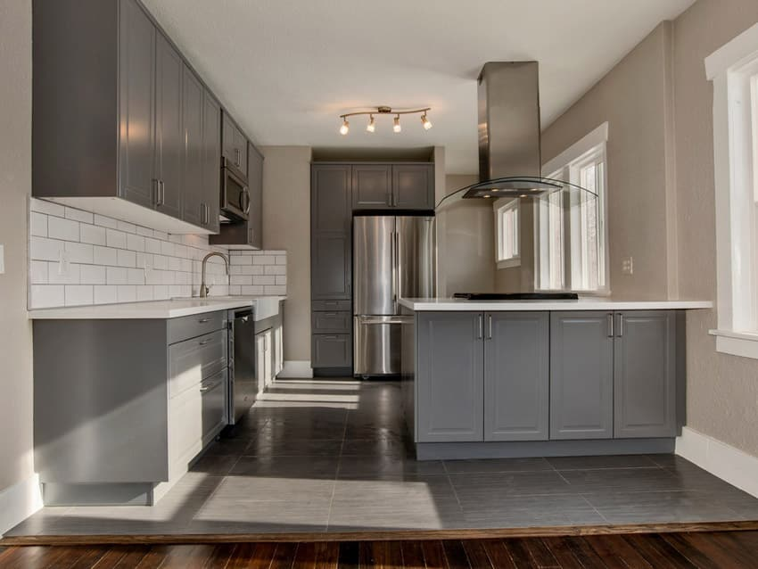 Compact closed kitchen with grey cabinets and white countertops