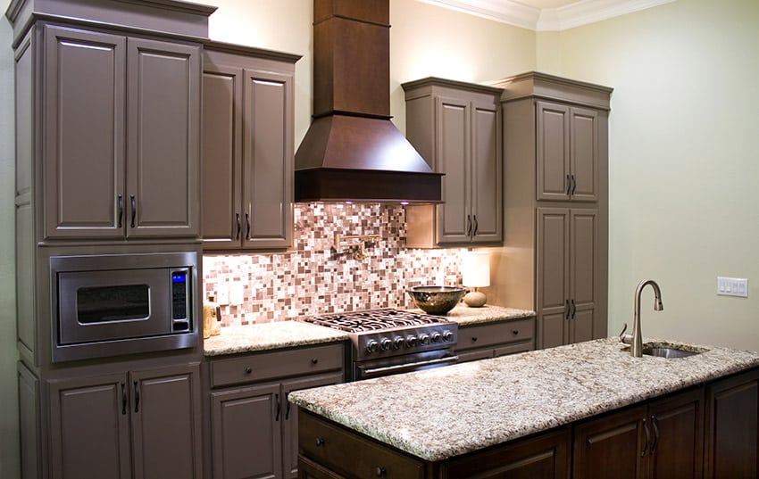 Compact kitchen with granite counter island, dark cabinets and mosaic tile backsplash
