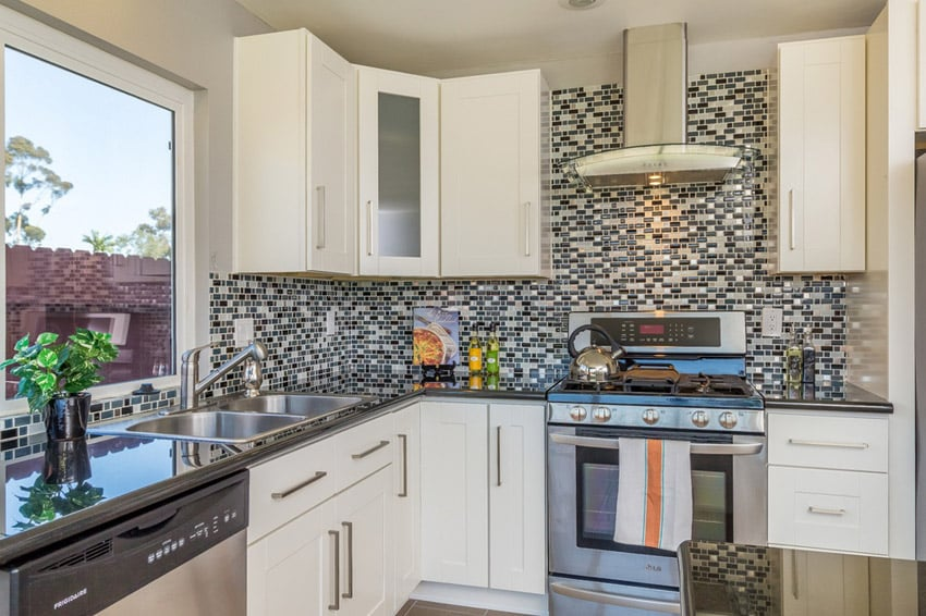 Compact kitchen with glass mosaic tile wall backsplash, white cabinets, dark counters