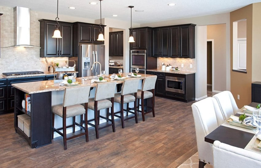 Compact traditional kitchen with island dark cabinets pendant lights