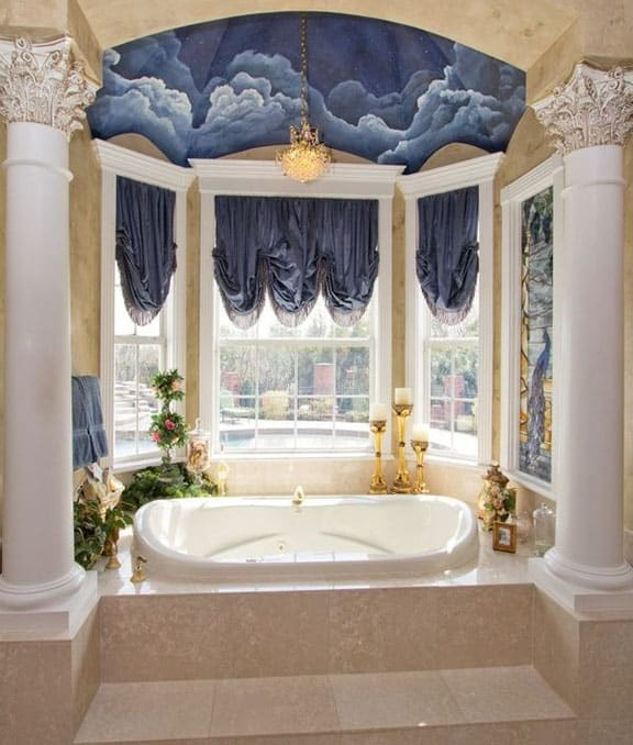 Elegant bathroom with pillars and ceiling mural with gold chandelier