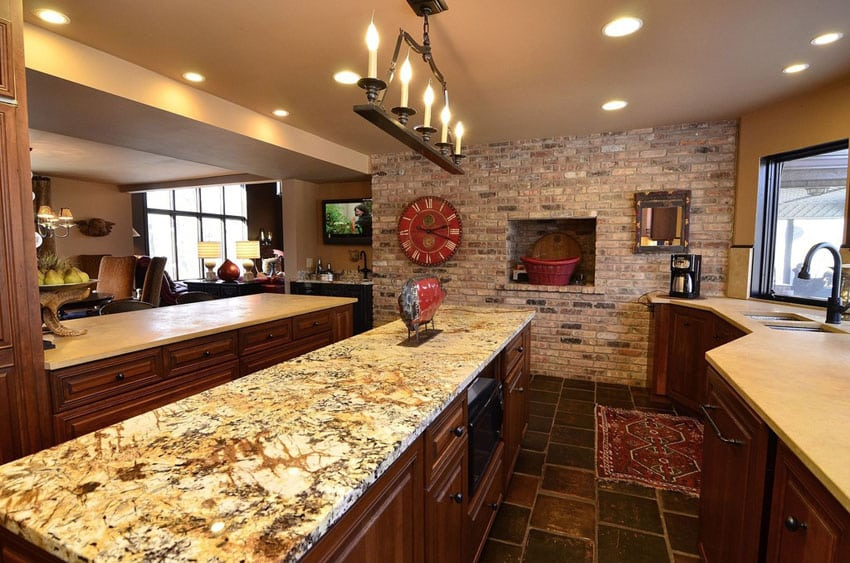 Galley style kitchen with light granite counter and brick accent wall