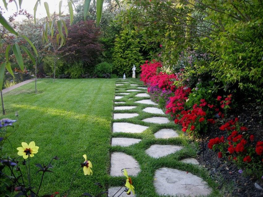 Irregular flagstone path through grass and garden flowers