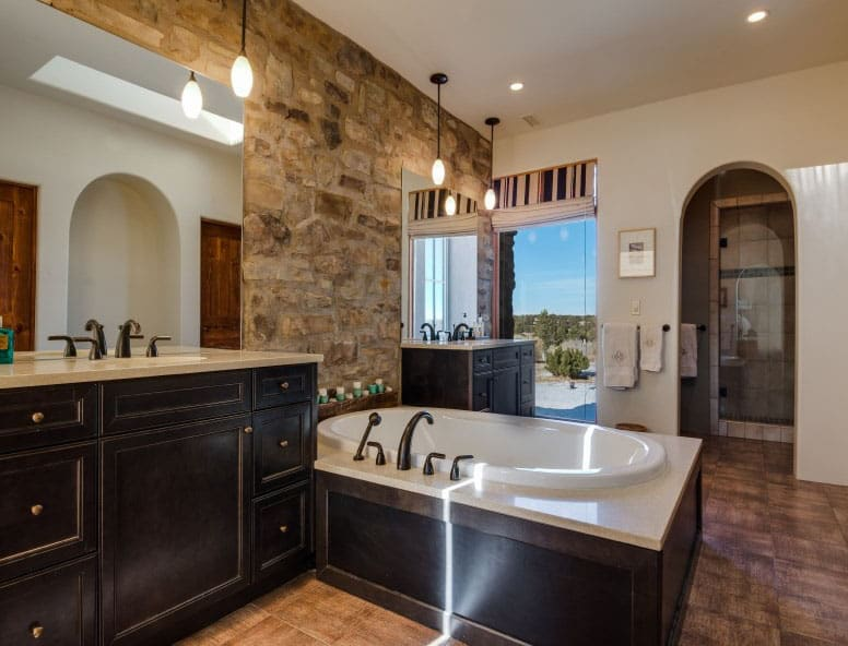 Master bath with rock wall and pendant lighting