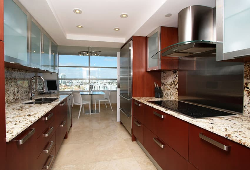 Modern galley kitchen with light granite counter in apartment