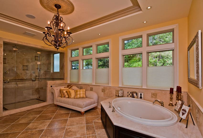 Muted luxury bathroom with chandelier, soaking bathtub, and daybed