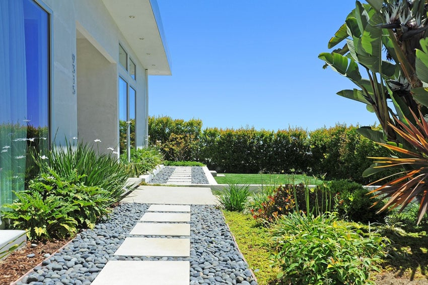 Pave stone patio walkway with river pebbles through backyard
