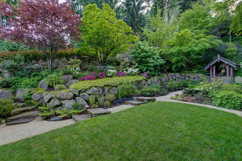 Rock garden path with granite slab steps through landscaped yard