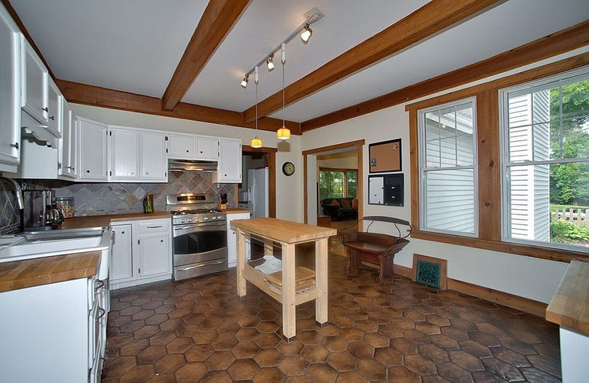Small wood portable island in kitchen with white cabinets