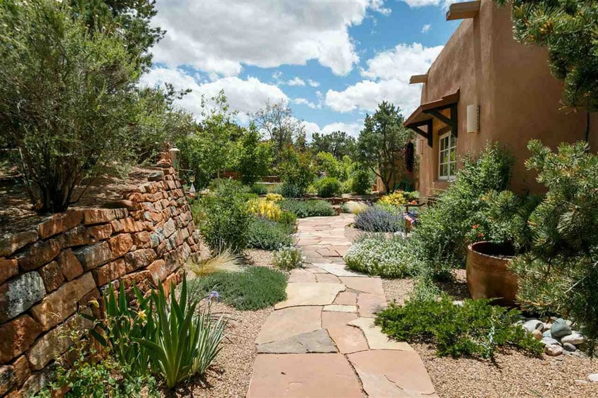 Stone floor path through backyard with stacked rock retaining wall