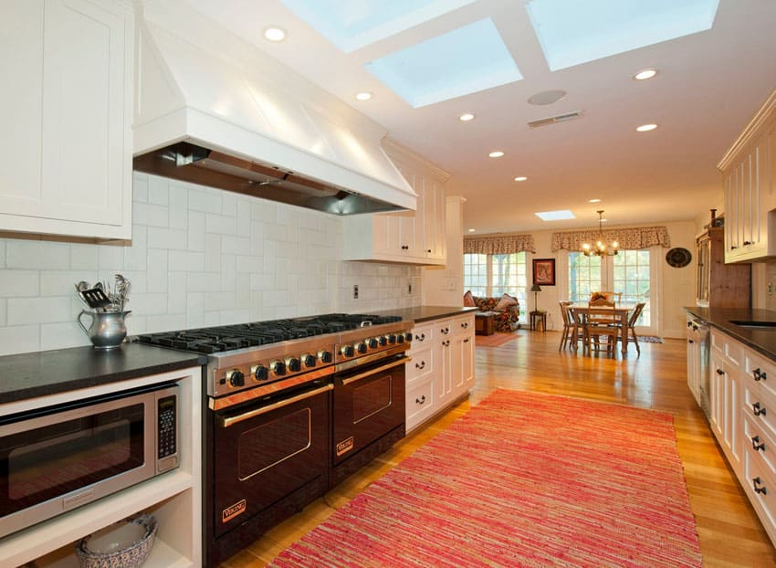 Traditional galley kitchen with white cabinets and skylight
