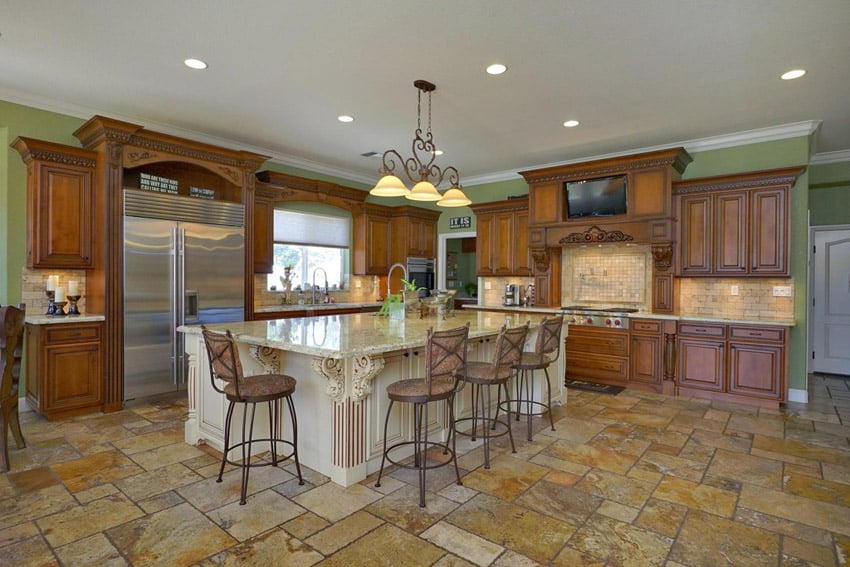 Traditional kitchen with rustic cabinetry, large island and travertine floor tiles