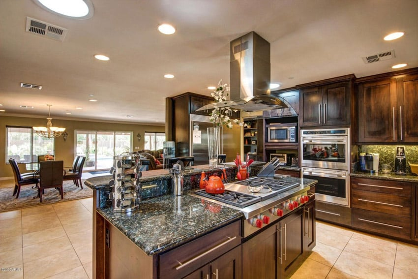 Traditional open plan kitchen with dark cabinetry and emerald granite