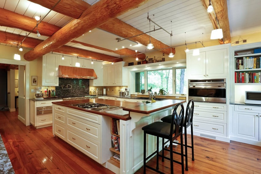 White cabinet kitchen with large exposed beams and butcher block wood counters