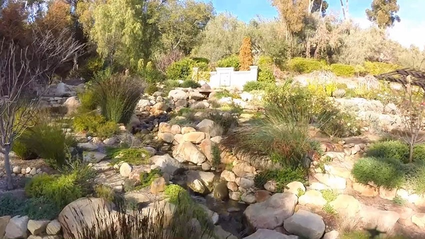 Backyard water feature stone river at luxury home