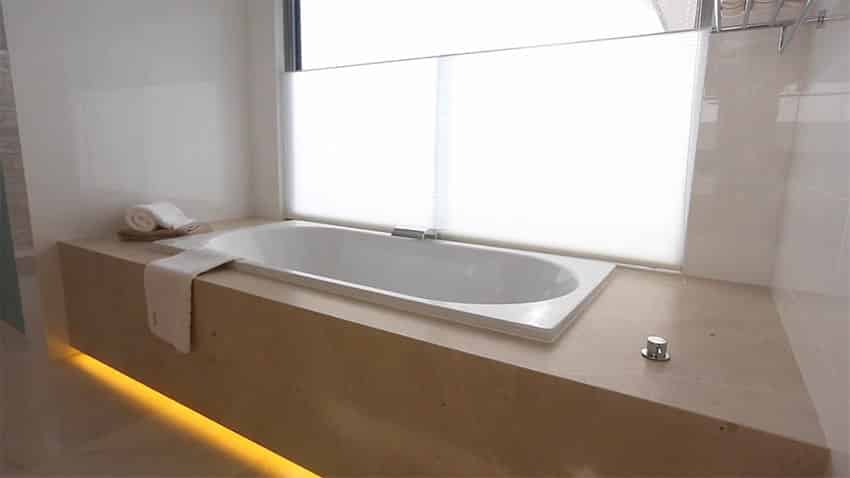 Bathtub in modern bathroom with under enclosure lighting
