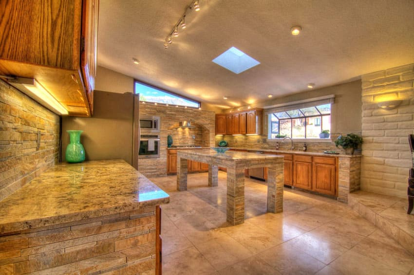 Contemporary kitchen with clay brick wall and stacked stone backsplash