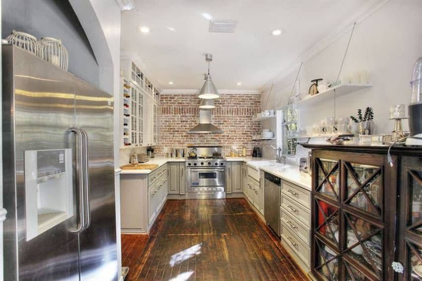 Country kitchen with brick wall and white cabinets