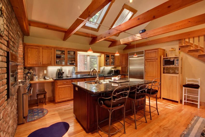 Country kitchen with high arched ceiling with exposed beams and brick wall