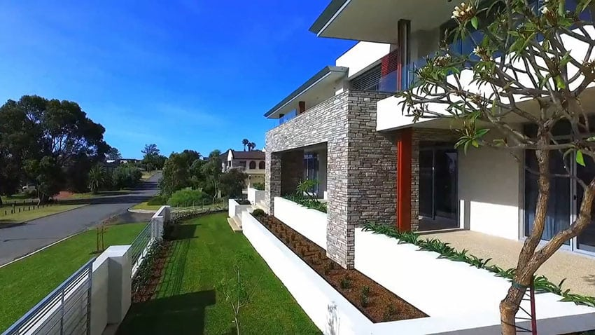 Front yard of modern house with stone walls and balcony