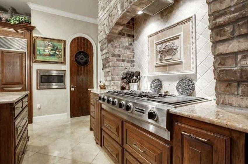 Kitchen with marble tile backsplash and brick veneer