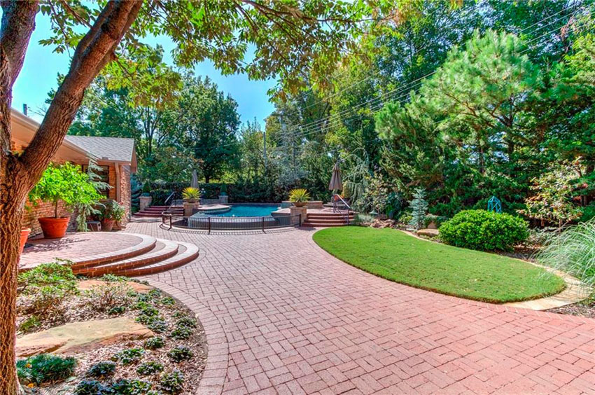 Landscaped patio area with red paver bricks leading to swimming pool