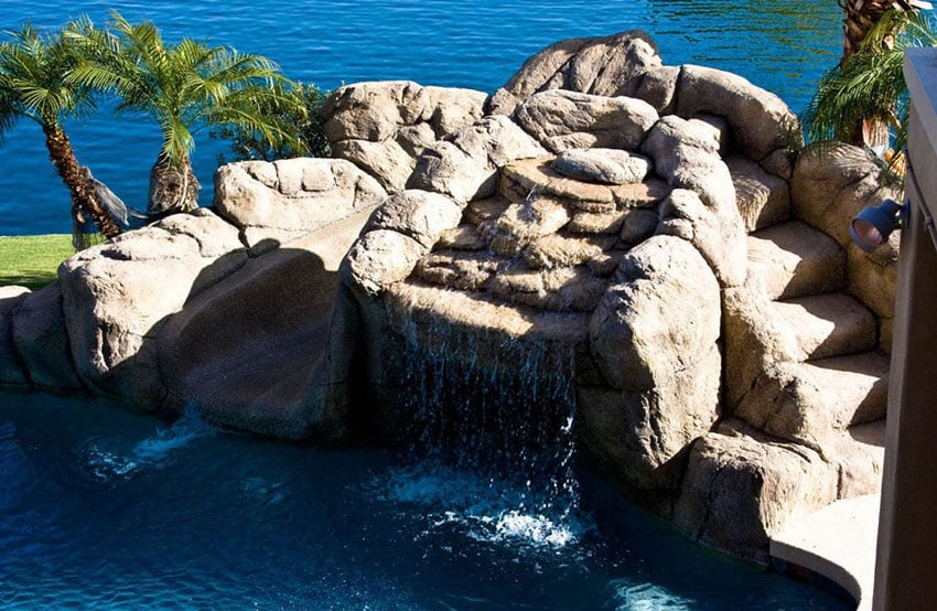 Large rock waterfall water feature in swimming pool
