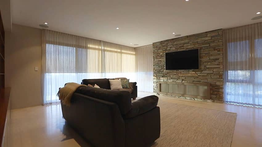 Movie room in modern home with stacked stone wall